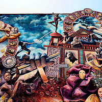 Theatre of Life Mural by Meg Saligman and Juan Dimida in Philadelphia, Pennsylvania<br /> Since 1984, the &ldquo;Mural Arts Program&rdquo; has sponsored over 3,600 wall murals from more than 300 artists. The average project in Philadelphia ranges from $10,000 to $15,000. What started as an anti-graffiti effort has blossomed into the world&rsquo;s largest outdoor gallery in the City of Brotherly Love. Several walking tour options are available. During the Center City tour, you will pass this mural on Broad and Lombard Streets. &ldquo;Theatre of Life&rdquo; was created by Meg Saligman and Juan Dimida. The art represents people&rsquo;s different roles. Notice the two hands holding marionette sticks. They symbolize external influences controlling people. In addition to 400 gallons of paint, it consists of 10,000 glass pieces, a ton of concrete and 5,000 marbles. The gorgeous mural was completed in 2002.