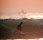 A surfer takes a wave near a fishing boat at Dreamland, Bali, Indonesia.