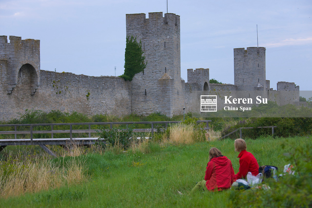 Tourists watch medieval city wall and tower, Visby, Gotland Island, Sweden