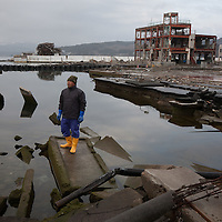 Koji Saito, a fisherman, stands on rubble which marks the location where his house used to be, before it was destroyed by the March 3rd 2011 tsunami, on the 1 year anniversary of the March 11th 2011 earthquake and tsunami, in Minami-Sanriku, Tohoku region, Japan on Sunday 11th March 2012.