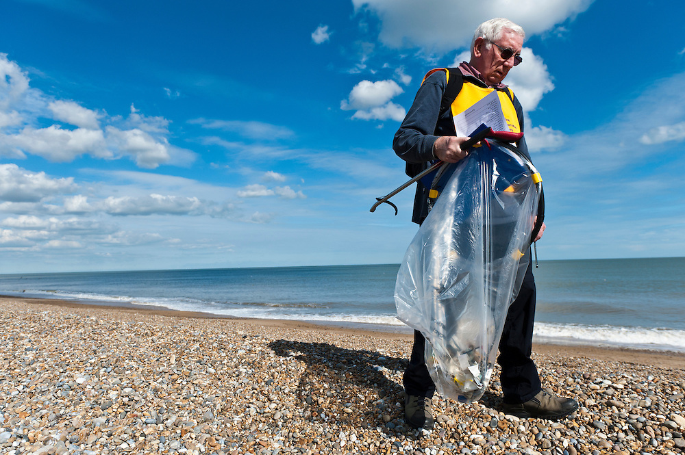 Volunteer collecting rubbish during a beach clean-up organised by the Marince Conservation Society, Aldeburgh, Suffolk, UK, 2010.