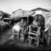 Cameroon/CAR refugees/ TO GO WITH BAPTISTE DE CAZENOVE'S STORY / CAR refugees try to protect themselves again the rain, on november 06, 2014 at the Gado's market place. /UNHCR/O.Laban-Mattei/November 2014