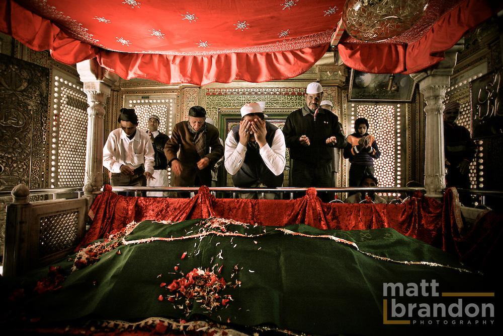 Men pray over the tomb of Hazrat Nizamuddin Chisty.