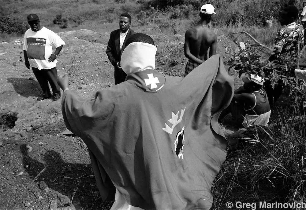 IPMG0115 South Africa, Ngwelezana 2000: .A Lutheran priest dons his vestments prior to the funeral of AIDS activist Deli Hlongwa in Ngwelezana in the KwaZulu Natal province of South Africa, March 25, 2000 on the day of her funeral.  Deli was a person living with full-blown AIDS who took part in the local `Funeral Campaign' where people with HIV and Aids tell others in he community of their disease and invite them to come look at them in their open casket when they die, to disprove the widely-held notion that HIV does not kill.  South Africa has a rapidly growing HIV crisis, with some 25% of ante-natal women testing positive.  .Photograph by Greg Marinovich/South Photographs