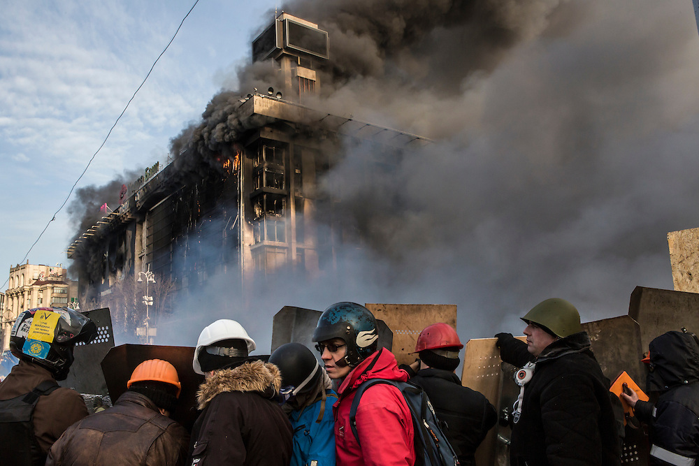 KIEV, UKRAINE - FEBRUARY 19: Anti-government protesters guard the perimeter of Independence Square, known as Maidan, as the Trade Unions Building, which has served as the de facto headquarters for the protest movement, burns on February 19, 2014 in Kiev, Ukraine. After several weeks of calm, violence has again flared between police and anti-government protesters, who are calling for the ouster of President Viktor Yanukovych over corruption and an abandoned trade agreement with the European Union. (Photo by Brendan Hoffman/Getty Images) *** Local Caption ***