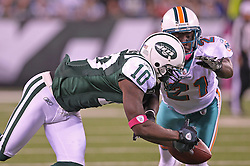 October 17, 2011; East Rutherford, NJ, USA; Miami Dolphins cornerback Vontae Davis (21) breaks up a catch by New York Jets wide receiver Santonio Holmes (10) during the first half at the New Meadowlands Stadium.