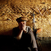 Safoullah, 26, a Northern Alliance solider, sits on the floor of a bunker while bullets fired by Taliban soldiers zip over his sanctuary in this October 14, 2001 photo.