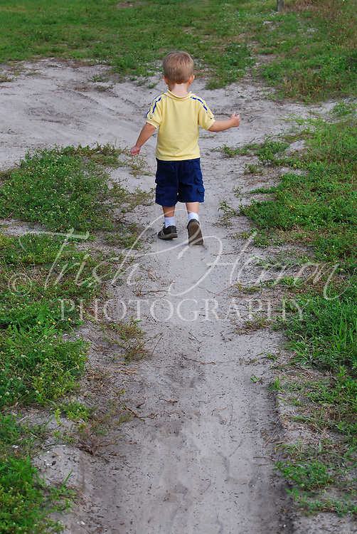 A small boy walks away on a sandy path.