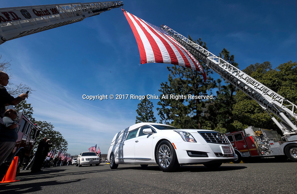 The hearse carrying the body of Whittier Police Officer Keith Boyer passes under a giant U.S. flag at Rose Hills Memorial Park in Whittier, Calif., Friday March 3, 2017. Boyer, who was fatally shot after responding to a traffic crash, was remembered today by thousands of law enforcement officers, friends and family as a dedicated public servant, talented drummer, loving friend and even a ``goofy'' dad.<br /> (Photo by Ringo Chiu/PHOTOFORMULA.com)<br /> <br /> Usage Notes: This content is intended for editorial use only. For other uses, additional clearances may be required.