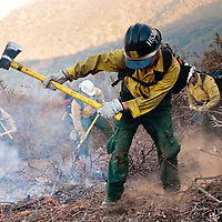 """A woman on the Chuchupati Flight Crew 530 uses her """"Pulaski"""" tool to clear a circle around a spot fire that jumped over the fire break at the La Brea Fire."""