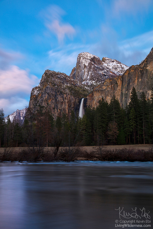Bridalveil Fall, a 620-foot (189-meter) waterfall, is partially reflected in the Merced River at dusk in this scene from Valley View in Yosemite National Park, California.
