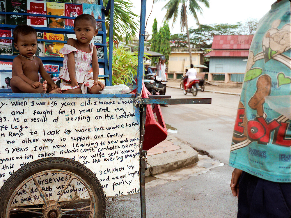 The children of a soldier who lost his leg to a landmine sell books about Angkor and the Khmer Rouge to tourists in Siem Reap.