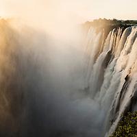 Africa, Zambia, Mosi-Oa-Tunya National Park,  Setting sun lights mist-covered Eastern Cataract of Victoria Falls