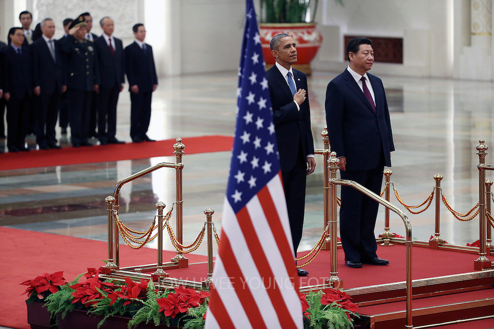 epa04485890 US President Barack Obama (2-R) and Chinese President Xi Jinping (R) stand at attention during the US national anthem during a welcome ceremony at the Great Hall of the People (GHOP) in Beijing, China, 12 November 2014. Obama is in China to attend the Asia-Pacific Economic Cooperation (APEC) 2014 Summit and related meetings.  EPA/HOW HWEE YOUNG