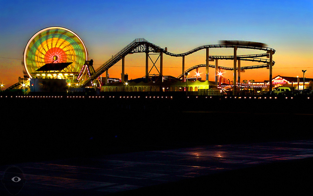 Sunset illuminates the neon lights and roller coaster about the Santa Monica Pier on the California coast.