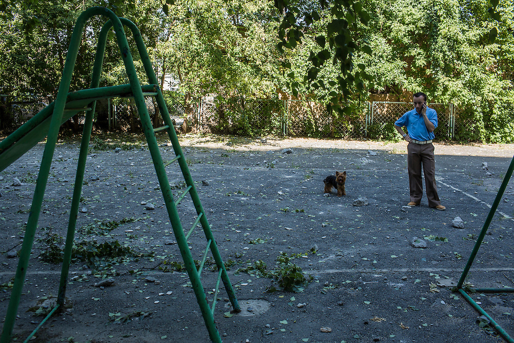 A man with a dog talks on the telephone amid rubble from suspected grad rocket strikes on an apartment building on Tuesday, July 29, 2014 in Donetsk, Ukraine.