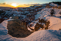 The curved canyon rim leads to the snow covered hoodoos in Bryce Canyon National Park during a Winter sunrise.