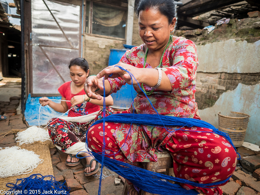 02 AUGUST 2015 - BHAKTAPUR, NEPAL:  Women make tourist curios in front of their temporary shelters in Bhaktapur. The Nepal Earthquake on April 25, 2015, (also known as the Gorkha earthquake) killed more than 9,000 people and injured more than 23,000. It had a magnitude of 7.8. The epicenter was east of the district of Lamjung, and its hypocenter was at a depth of approximately 15km (9.3mi). It was the worst natural disaster to strike Nepal since the 1934 Nepal–Bihar earthquake. The earthquake triggered an avalanche on Mount Everest, killing at least 19. The earthquake also set off an avalanche in the Langtang valley, where 250 people were reported missing. Hundreds of thousands of people were made homeless with entire villages flattened across many districts of the country. Centuries-old buildings were destroyed at UNESCO World Heritage sites in the Kathmandu Valley, including some at the Kathmandu Durbar Square, the Patan Durbar Squar, the Bhaktapur Durbar Square, the Changu Narayan Temple and the Swayambhunath Stupa. Geophysicists and other experts had warned for decades that Nepal was vulnerable to a deadly earthquake, particularly because of its geology, urbanization, and architecture.      PHOTO BY JACK KURTZ