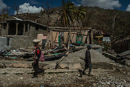 "RENDEL, HAITI - OCTOBER 12, 2016: People from Rendel walk past destroyed houses, leaving town with bags of their belongings. ""Ninety percent of our village is gone,"" said Eric Valcourt, a priest in the Catholic parish that runs the local clinic and school, which now houses those too sick or poor to leave.  ""Many left by foot to escape the disease and devastation. The rest died from Cholera or the hurricane.""  Thousands have taken the journey of more than three hours by foot, forging a waist-high river that bends so often that it requires 9 crossings along the way.  They carry with them their remaining belongings: split bags of clothes on their heads, small livestock in their arms. They carry disease too, destined for towns connected to the rest of the country by road."