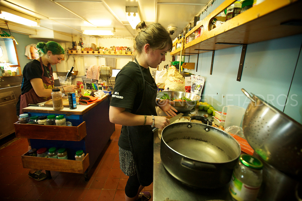 (R) Karlie Darlington assists (L) head chef Tamara Scoulidis preparing a big lunch in the kitchen of Seashepherd's 'Steve Irwin'. The girls are in charge of the vegan kitchen and make 3 meals a day for the 20 crew. During Operation Kimberley Miinimbi, they even managed to create lunch for 20 VIP's who came on board during the day, to watch the Whales at James Price Point. Broome, WA