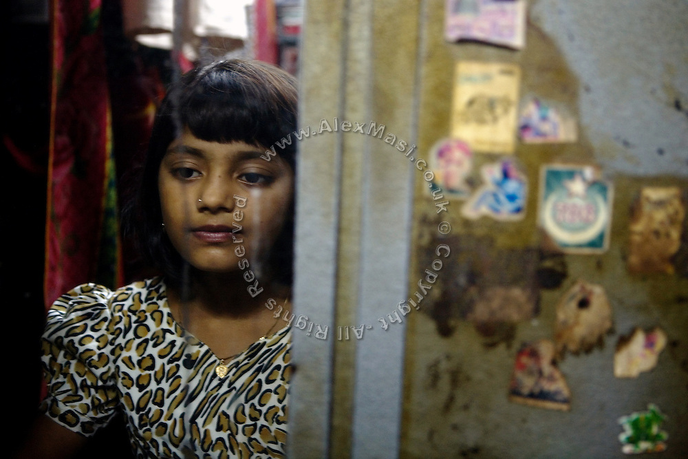 Rubina Ali, 9, the child actor playing the role of 'young Latika', the friend/lover of Jamal, protagonist of Slumdog Millionaire, the famous movie winner of 8 Oscar Academy Awards in December 2008, is looking at the mirror inside her uncle's house in the slum where she still lives with her family next to the train station of Bandra (East), Mumbai, India. Various promises were made to lift the two young actors (Azharuddin Ismail and Rubina Ali) from poverty and slum-life but as of the end of May 2009 anything is yet to happen. Rubina's house was recently demolished with no notice as it lay on land owned by the Maharashtra train authorities and she is now permanently living with her uncle's family in a home a stone-throw away in the same slum. Azharuddin's home too was demolished in the past two weeks, as it happens every year in his case, because the concrete walls were preventing local authorities to clear a drain passing right behind it. As usual, his father is looking into restoring the walls as soon as the work on the drain has been completed.