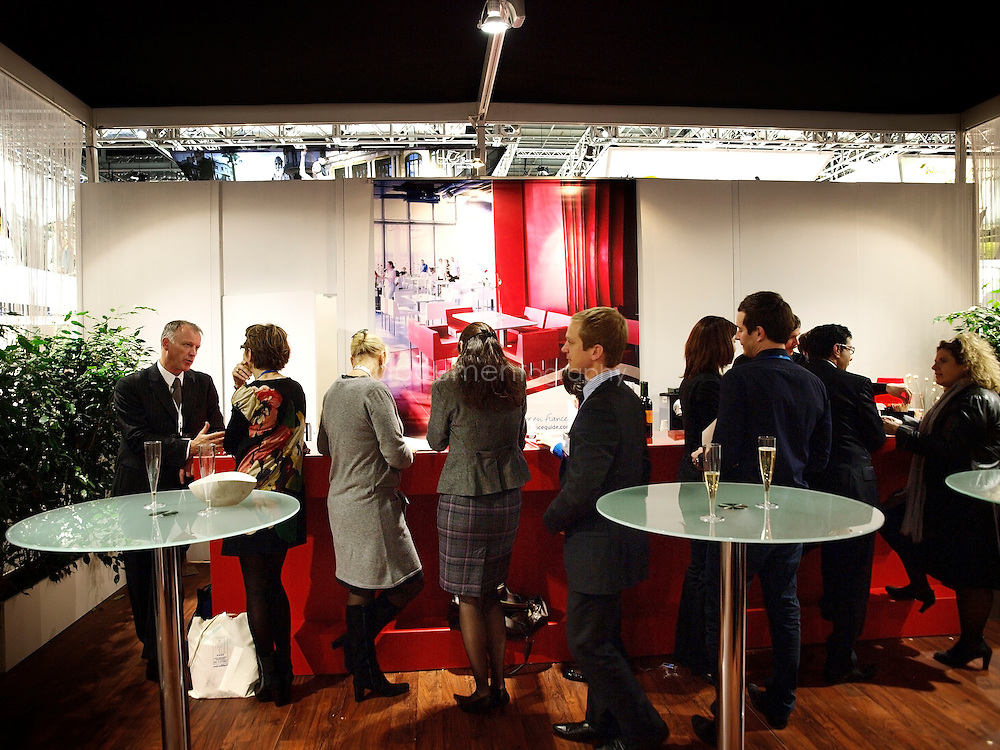 People enjoy champagne as they network at the bar of the french stand at the World Travel Market, ExCel, London, UK.