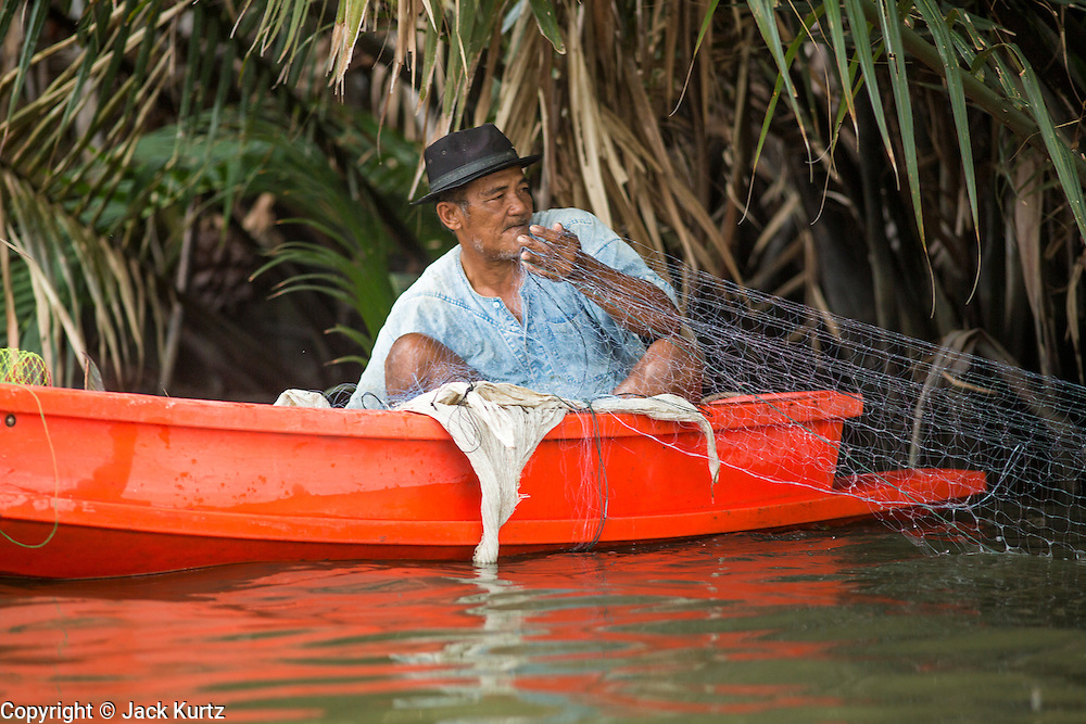"17 NOVEMBER 2012 - BANGKOK, THAILAND:  A man in a small fiberglass boat pulls in his fishing net from a canal in the Thonburi section of Bangkok. Bangkok used to be known as the ""Venice of the East"" because of the number of waterways the criss crossed the city. Now most of the waterways have been filled in but boats and ships still play an important role in daily life in Bangkok. Thousands of people commute to work daily on the Chao Phraya Express Boats and fast boats that ply Khlong Saen Saeb or use boats to get around on the canals on the Thonburi side of the river. Boats are used to haul commodities through the city to deep water ports for export.    PHOTO BY JACK KURTZ"