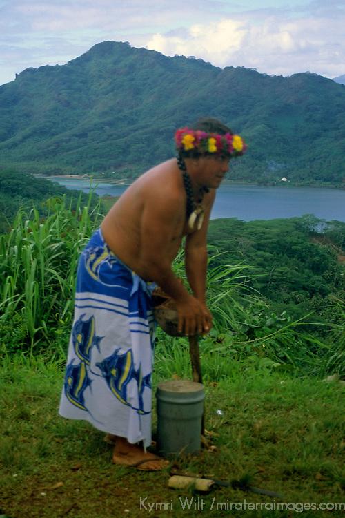 French Polynesia,Tahiti, Taha'a. Tahitian islander demonstrates opening a coconut.