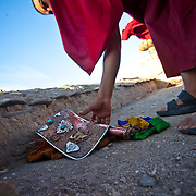 A Ladakhi monk reaches for his ceremonial conch  shell horn.
