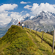 """Two hikers on Wasenegg Ridge, in view of the Wetterhorn, Eiger, Monch & Jungfrau mountains in the Berner Oberland, Switzerland.  Published in Ryder-Walker Alpine Adventures """"Inn to Inn Alpine Hiking Adventures"""" Catalog 2007, 2009, 2011, 2012, 2013."""