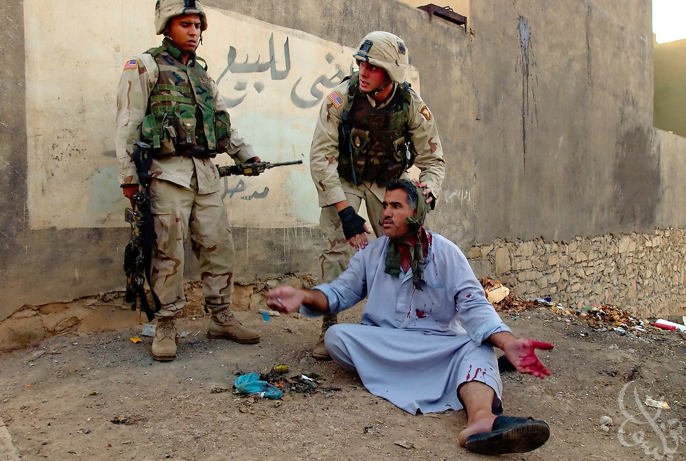 US Army 101st Airborne troops treat a wounded Iraqi suspect after shooting him July 23, 2003 in the neck, a block from the site where U.S. forces killed both Ouday and Qusay Hussein in Mosul, Iraq yesterday.