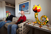 American artists Phillip Maberry & Scott Walker, known as Phillip and Scott, at their new home in Landers, California. .from left to right: Scott Walker & Phillip Maberry.For over twenty-five years they have created one-of-a kind ceramic sculptures, hand glazed tiles, reliefs and objects for gallery and museum installations as well as having fulfilled numerous residential and commercial commissions. Their emphasis has always been on modern interpretations of past decorative styles, infused with an optimistic spirit...Text by Claudia Steinberg - full text available from the author:.For the past three decades, American artists Phillip Maberry and Scott Walker have collaborated on quirky, beautiful ceramic objects and tiles. They invested years of their lives building from scratch a stunning three-story house in the Catskills that accommodated giant boulders in its interior.  Once they were done with the time-consuming ceramic decoration of their new home they grew restless. Tired of the long cold winters and humid summers in Highland, NY, they began looking for a place in the sun. After a brief stay in Los Angeles they fell in love with the Mojave desert and decided to build a house with a view of a grand mountain. A New York based architect helped the couple design a stainless steel structure which was shipped to California by train and assembled on site, while the two men lived in a small trailer. It took almost a year to install the house on the ever-shifting sand dune they had inadvertently chosen as their foundation. In the meantime Maberry and Walker have planted their own glow-in-the-dark ceramic mushrooms in their sandy garden, and their charming porcelain creatures based on blow-up beach toys lurk everywhere. Curiously,  their new home has the same modernist, elegant esthetic as their previous house.