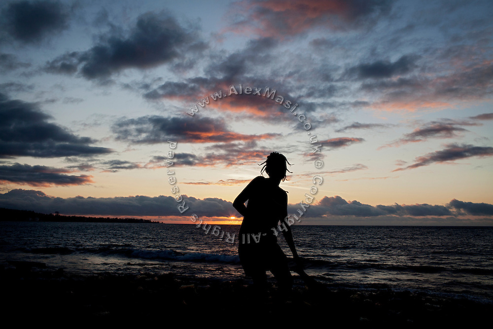 At sunset, a young woman is collecting dry clothes in Roça Ribeira Funda, on the island of Sao Tome, Sao Tome and Principe, (STP) a former Portuguese colony in the Gulf of Guinea, West Africa.