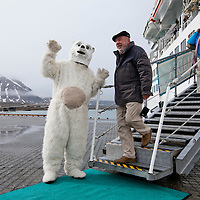 Norway, Svalbard, Ny Ålesund, Passengers from cruise ship Amadea pose for souvenir snapshots with costumed polar bear at dock in small arctic research station