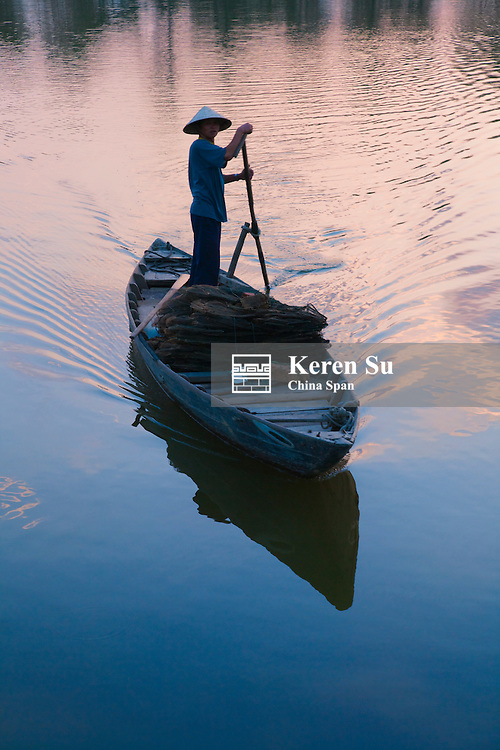 Girl with conical hat rowing boat on Thu Bon River at sunset.