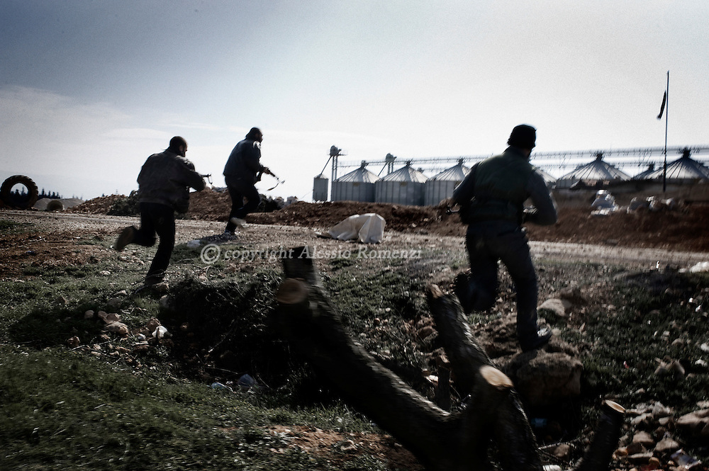 SYRIA - Al Qsair. Free Syrian Army fighters run to approach a former Al Asad Forces position in the outskirts of Al Qsair, on February 24, 2012. ALESSIO ROMENZI