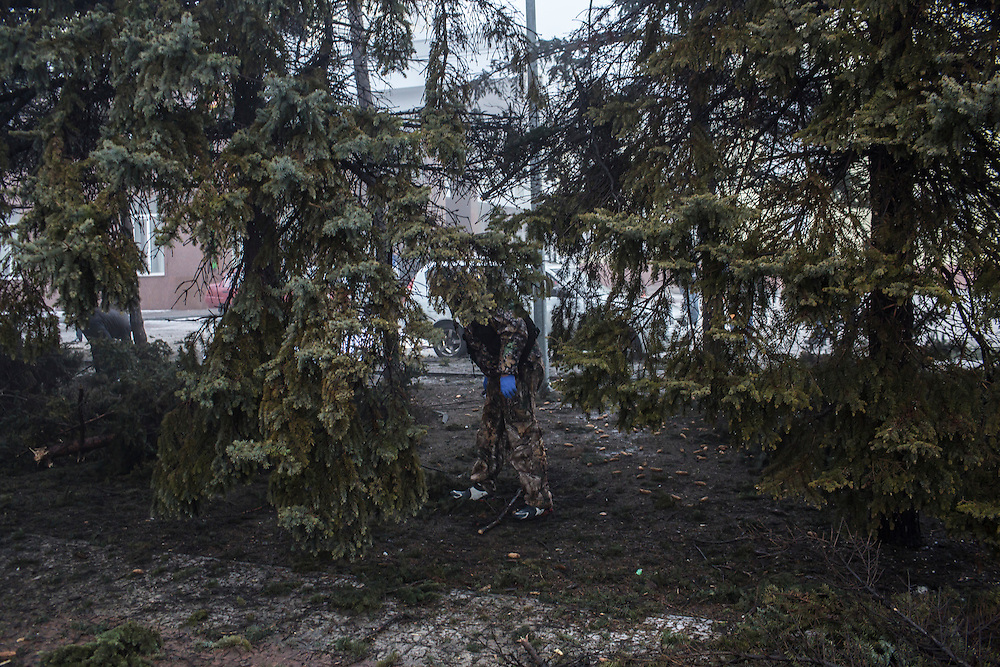 DONETSK, UKRAINE - JANUARY 30, 2015: An investigator searches for evidence at the scene of a rocket attack that killed at least five people when it struck the parking lot near a humanitarian aid distribution center in Donetsk, Ukraine. At least two others died in a separate shelling nearby. CREDIT: Brendan Hoffman for The New York Times