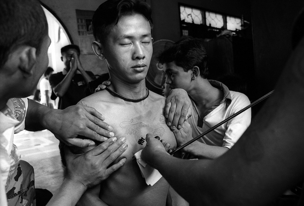 Tattoo Festival at Wat Bang Phra, a Buddhist temple in the town of Nakhorn Chaisri, Thailand - men adorned by Thai Monks with tattoos representing animal spirits often go into a trance claiming they are possessed  by the spirit of the animal. March 2003..©David Dare Parker/AsiaWorks Photography.