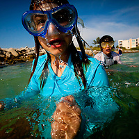 Alexys McCarthy, 10, comes up while searching for crabs and shells along the seawall at Pass-A-Grille Beach in St. Petersburg.