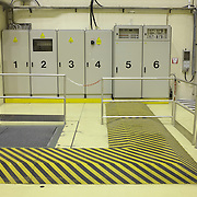 Striped covers for electrical cables turn a right-angle turn to the left towards power cabinets  which are numbered 1 to 6 at the European Space Agency's Europropulsion Ariane 5 rocket Booster Integration Building. Railings ensure that pedestrians keep to the  walkways without endangering health and safety, according to EU law. Elsewhere in this giant building the boosters that propel ESA rockets into space are integrated with their payloads.  ...