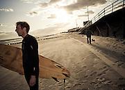 A surfer surveys the waves while a man walks his dog near the boardwalk, Rockaway Beach, Queens, NY.