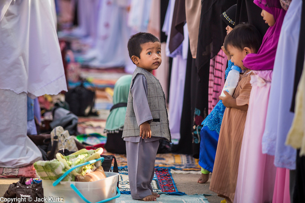 A child walks between lines of adults during Eid services at Songkhla Central Mosque in Songkhla province of Thailand. Eid al-Fitr is also called Feast of Breaking the Fast, the Sugar Feast, Bayram (Bajram), the Sweet Festival and the Lesser Eid, is an important Muslim holiday that marks the end of Ramadan, the Islamic holy month of fasting.