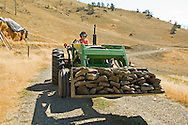Mature woman drives tractor with load of rocks, <br /> MODEL RELEASED, PROPERTY RELEASED