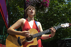 """London, July 18th 2015. Regular Southbank busker Emily Lee sings songs from her recently released EP """"Don't Forget To Love"""" on the Busking Bus as part of the Busk in London Festival aimed at showcasing the outstanding talents of many of the capital's finest street performers, including, musicians, magicians, living statues jugglers and bands."""
