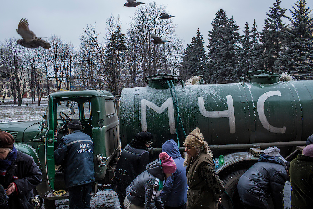 DEBALTSEVE, UKRAINE - FEBRUARY 7, 2015: People collect bottles of clean drinking water from trucks in Debaltseve, Ukraine. The Ukrainian-controlled town, surrounded on three sides by rebel forces, has been undergoing heavy shelling for more than a week, but a brief ceasefire allowed many residents to evacuate and others to simply venture out from their homes. CREDIT: Brendan Hoffman for The New York Times