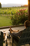 Couple enjoys a glass of wine overlooking vineyards at EdenVale Winery near Ashland, Southern Oregon