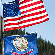 """The national flag of the United States and the state flag of Idaho fly from a mast. The Seal of the Territory of Idaho was adopted in 1863 and redrawn several times before statehood in 1890. The state Great Seal was designed by Emma Edwards Green, the only woman to design a state seal. The outer ring says """"Great Seal of the State of Idaho,"""" with the star signifying a new light in the galaxy of states. The inner ring contains a banner with the Latin motto, Esto perpetua (""""Let it be perpetual"""" or """"It is forever""""). A woman signifies justice, and a man dressed as a miner commemorates the chief industry in the 1890s. A shield shows a pine tree (timber interests), the Snake or Shoshone River, and a man plowing a field. A sheaf of grain and cornucopias (horns of plenty) portray bountiful agriculture.  An elk's head rises above the shield. The state flower (the wild Syringa or Mock Orange) and ripened wheat grow next to the woman."""