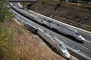 SANTIAGO DE COMPOSTELA, SPAIN - JULY 26: The first Renfe-Adif train service from Madrid since the accident passes next to the wreckage of the previous one on July 26, 2013 in Santiago de Compostela, Spain. The high speed train crashed after it derailed on a bend as it approached the north-western Spanish city of Santiago de Compostela at 8.40pm on July 24th. At least 78 people have died and a further 131 are reported injured. The crash occured on the eve of the Santiago de Compostela Festivities.  (© Pablo Blazquez)