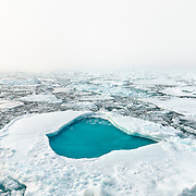 A pool of melt water collects on top of an ice floe in the Arctic Ocean during the lowest recorded sea ice levels in September, 2012.