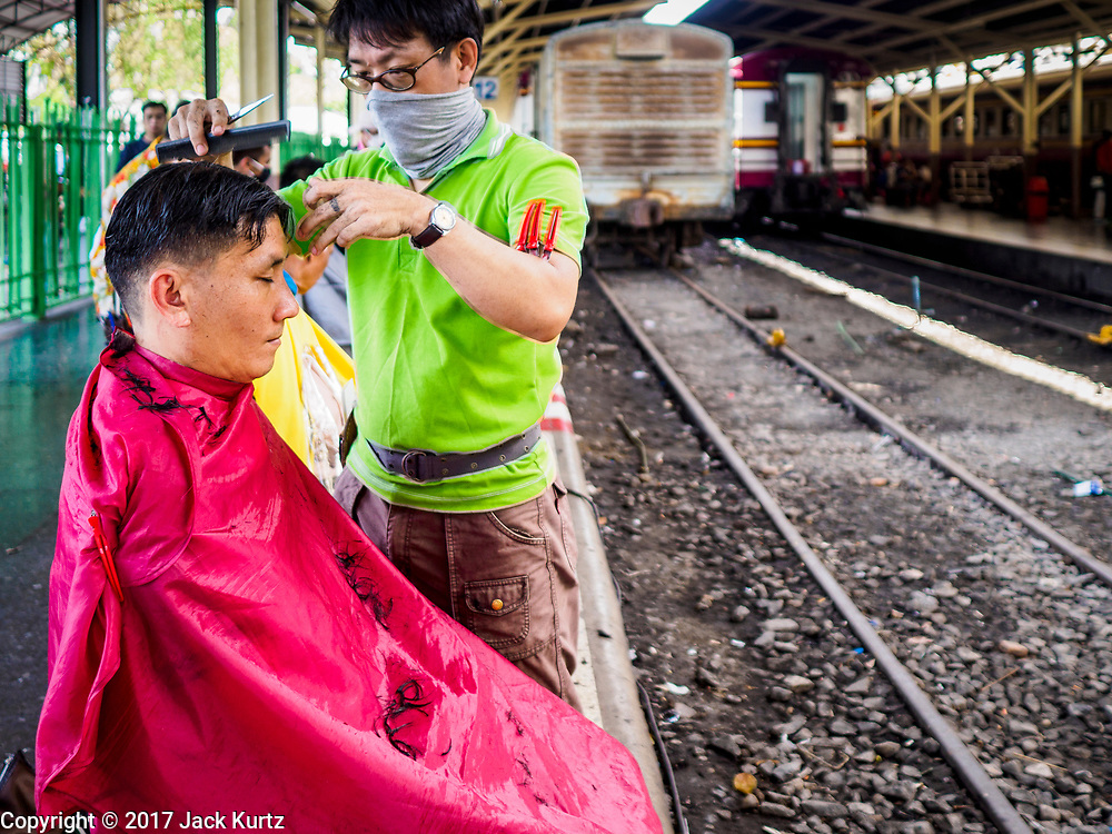 """11 APRIL 2017 - BANGKOK, THAILAND: Songkran travelers get free haircuts in Hua Lamphong train station during the Songkran travel period at Hua Lamphong train station in Bangkok. Songkran is the traditional Thai Lunar New Year. It is celebrated, under different names, in Thailand, Myanmar, Laos, Cambodia and some parts of Vietnam and China. In most places the holiday is marked by water throwing and water fights and it is sometimes called the """"water festival."""" This year's Songkran celebration in Thailand will be more subdued than usual because Thais are still mourning the October 2016 death of their revered Late King, Bhumibol Adulyadej. Songkran is officially a three day holiday, April 13-15, but is frequently celebrated for a full week. Thais start traveling back to their home provinces over the weekend; busses and trains going out of town have been packed.     PHOTO BY JACK KURTZ"""